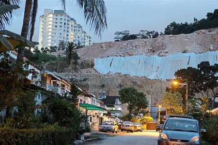 Prevention: Tarpaulin sheets covering a hill slope to stop erosion in Paya Terubong, Penang.
